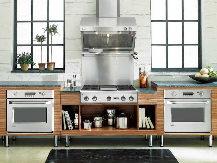 Instead of the double-height wall oven duo, this kitchen uses two wall ovens installed in the base cabinet space on either side of a pro-style cooktop. Photograph via GE Monogram.