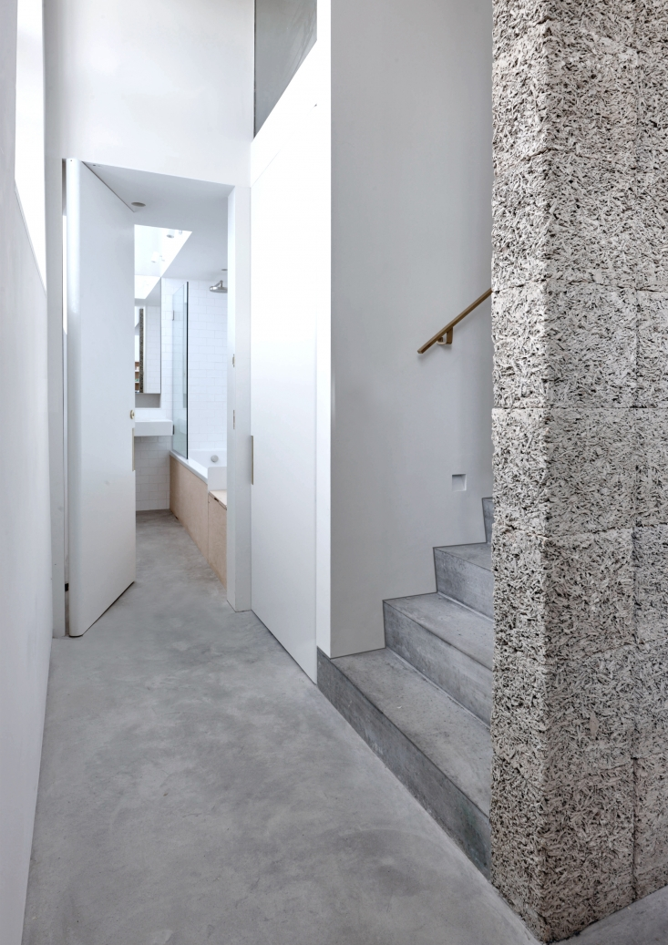 Another version of recycled wood-cement appears as the dramatic structural spine of the stairs. Also shown, a glimpse of the skylit downstairs bath, where polished concrete and plywood meet white tiles and glass.