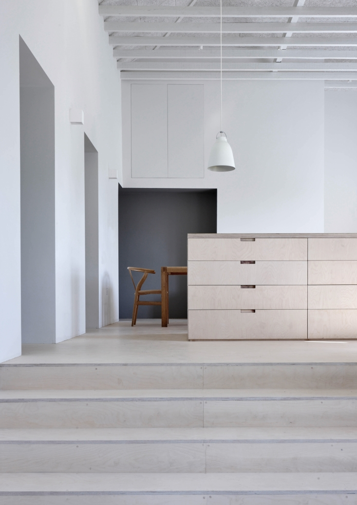 A Caravaggio P3 Pendant Light hangs over the central island, which like the steps, floor, and other cabinets are made of birch plywood finished with a clear matte oil.