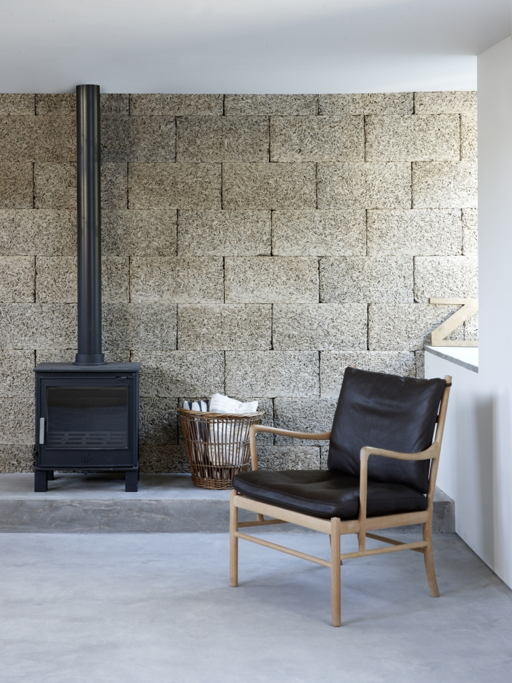 Textural wood wool blocks form the living room back wall and lend an intimacy to the space. (Also known as excelsior, these compressed strands of wood bonded with cement are traditionally used among other things as insulation.) The armchair is Ole Wanscher's 1949 149 Colonial Chair by Carl Hansen. For willow baskets similar to this one, see Object Lessons: Almighty Wicker Basket.