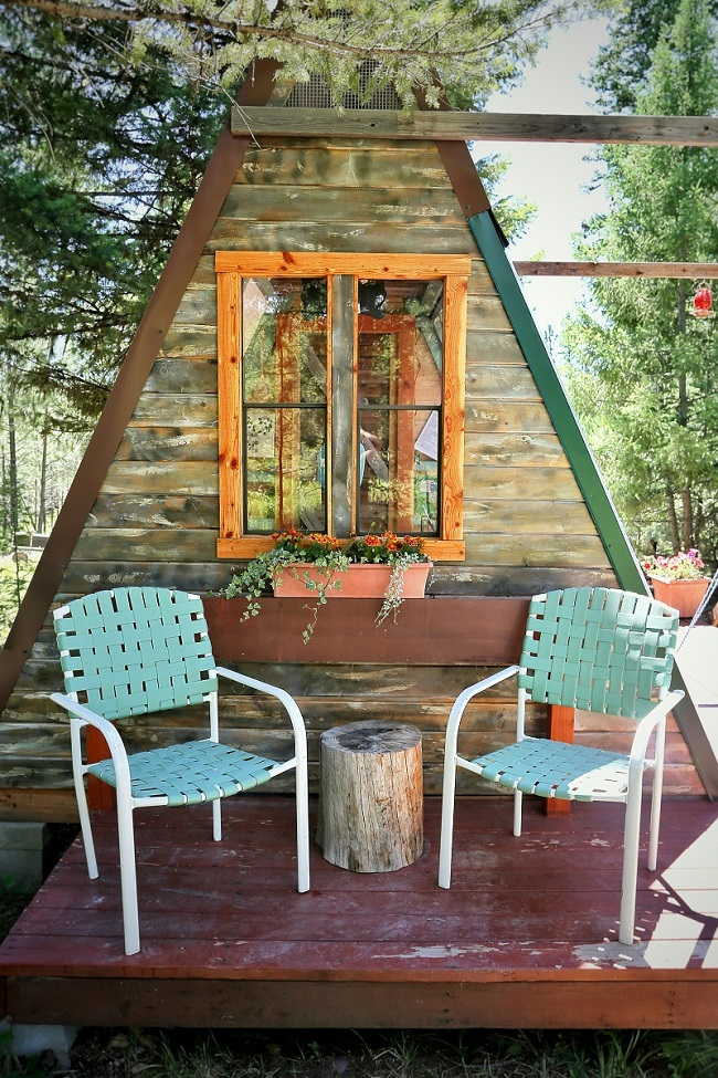 A-frame cabin with two chairs outside