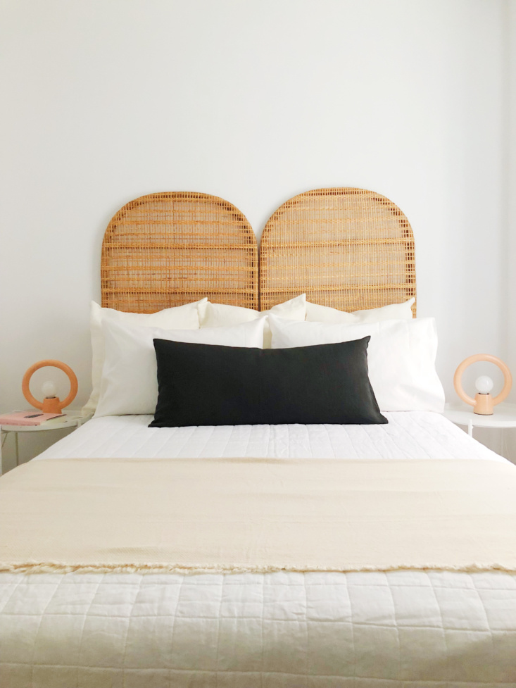 The Hoveys furnished a bedroom in the same apartment with an Ikea limited-edition rattan headboard and Urban Outfitters Ayo Ceramic Table Lamps—both since discontinued. The Belgian Linen Quilt, $249, is from West Elm and the dark gray Linon Pillow, $54.95, is from CB2.
