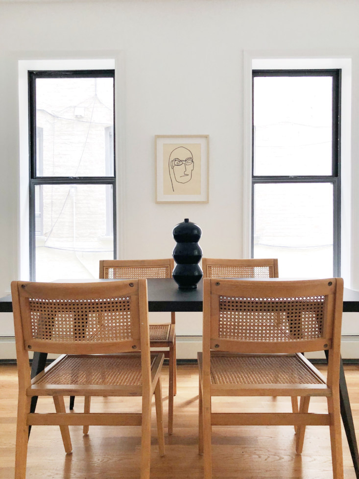 """For a Park Slope apartment staged on a tight budget (and sold with a furnishings purchase option), Hollister and Porter went with a palette of black, white, and wood. The rattan and rubberwood Marte Dining Chairs, $139 each, are from Urban Outfitters—""""they have a lot of cool organic-minimalist stuff lately."""""""