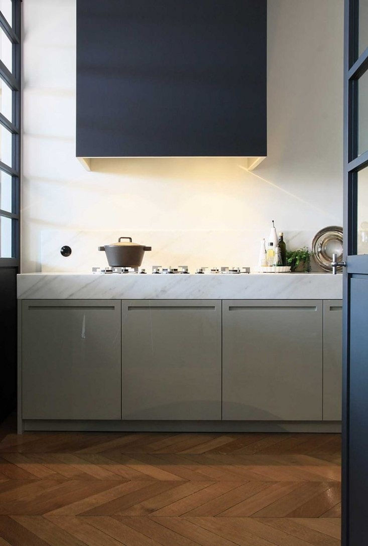 A cooktop is defined by a modernist hood in this kitchen by Netherlands-based Lodderkeukens.